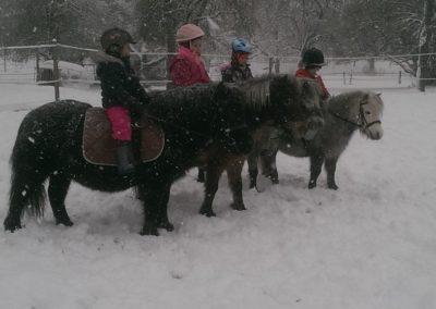 4 enfants sur leurs poneys en hiver