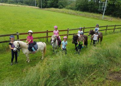 8 enfants à côtés de poneys
