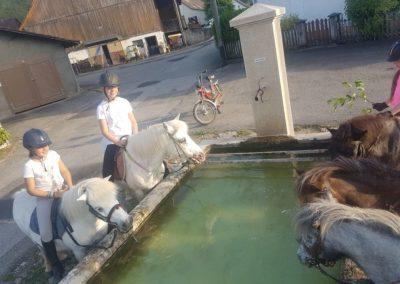 en ballade à poney devant une fontaine