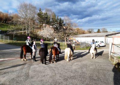 5 enfants sur leurs poneys et 1 enfant debout