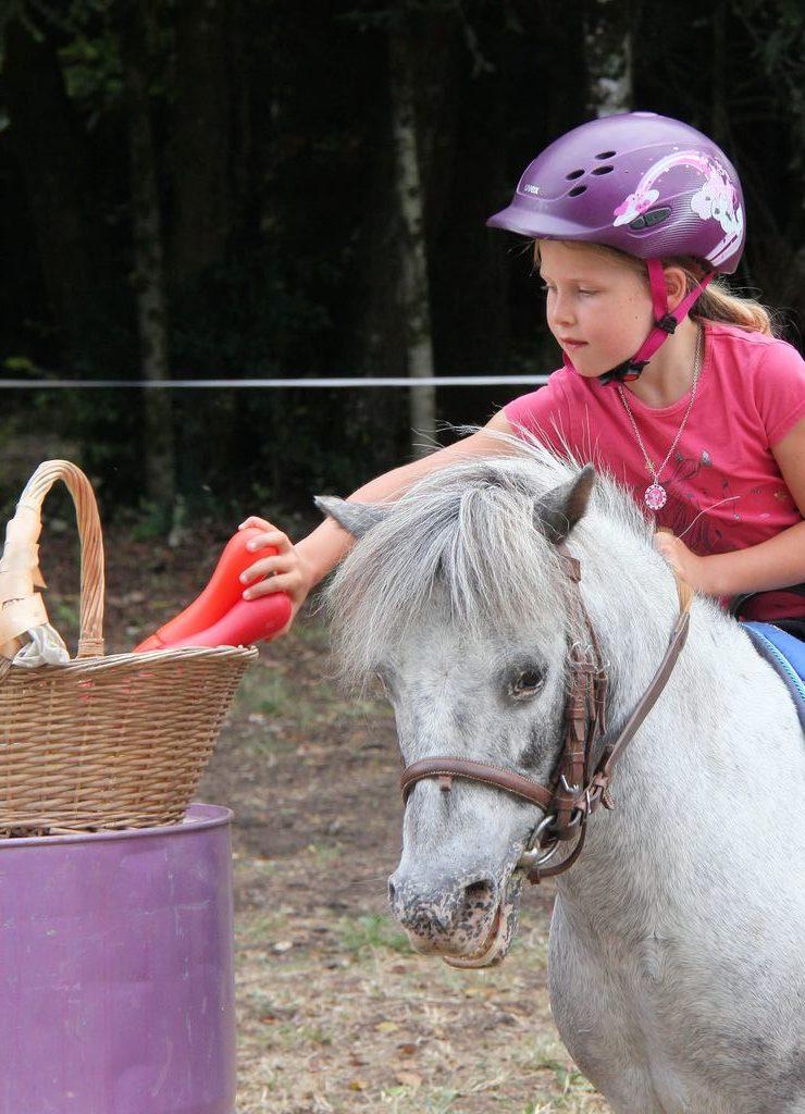 petite fille prend un objet sur son poney